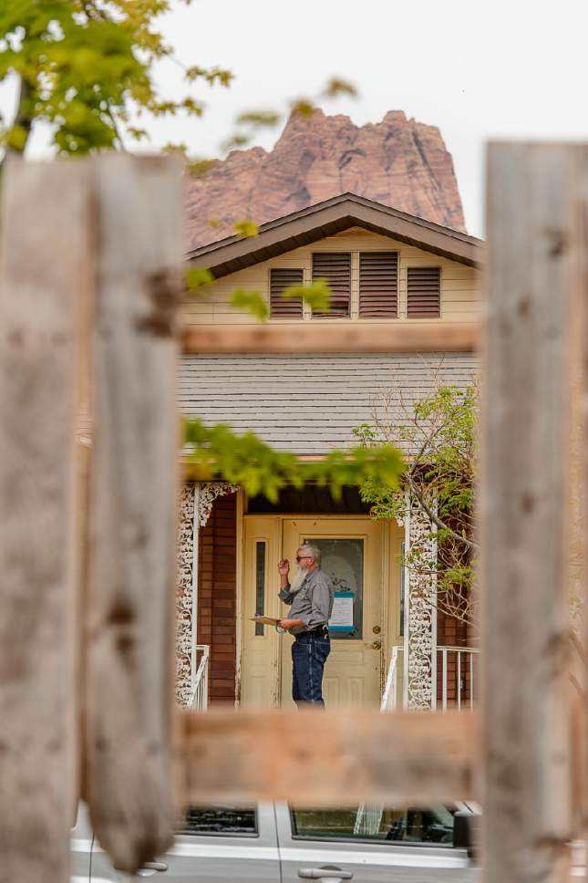 Trent Nelson  |  The Salt Lake Tribune Seen through a hole in a fence, Mohave County Constable Mike Hoggard checks a home for occupants during its eviction in Colorado City, Ariz., Tuesday May 9, 2017.