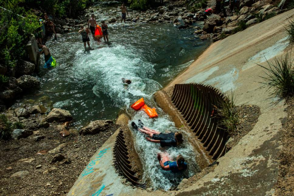 Chris Detrick  |  The Salt Lake Tribune Jenny Reese and her daughter Genevieve Reese, 11, of Salt Lake City, slide down a water tube in Parleys Creek in Parleys Historic Nature Park Sunday May 25, 2014.