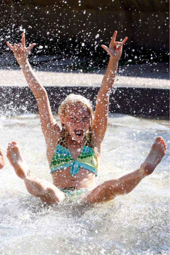 Rick Egan  |  Tribune file photo   9-year-old Heather Makestad splashes in the Seven Canyons Fountain at Liberty Park with her friends, trying to stay cool Monday, June 30,  2008.