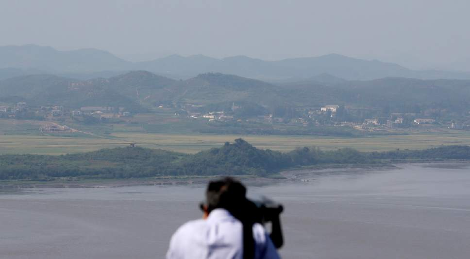 FILE - In this Sept. 9, 2016 file photo, a visitor uses binoculars to see the North Korean territory from the unification observatory in Paju, South Korea.  South Korea approved Friday, May 26, 2017, a civic group to contact North Korea over aid programs, the first such approval since North Korea's nuclear test in January 2016. (AP Photo/Lee Jin-man. File)