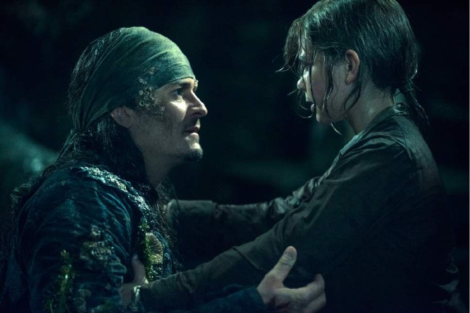 """In this image released by Disney, Orlando Bloom portrays Will Turner, left, and Lewis McGowen portrays young Henry Turner in a scene from """"Pirates of the Caribbean: Dead Men Tell No Tales."""" (Peter Mountain/Disney via AP)"""