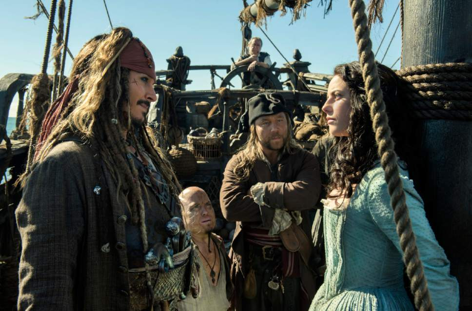 """In this image released by Disney, Johnny Depp portrays Jack Sparrow, left, and Kaya Scodelario portrays Carina Smyth, right, in a scene from """"Pirates of the Caribbean: Dead Men Tell No Tales."""" (Peter Mountain/Disney via AP)"""