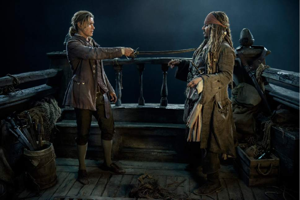 """In this image released by Disney, Brenton Thwaites portrays Henry Turner, left, and  Johnny Depp portrays Jack Sparrow in a scene from """"Pirates of the Caribbean: Dead Men Tell No Tales."""" (Peter Mountain/Disney via AP)"""