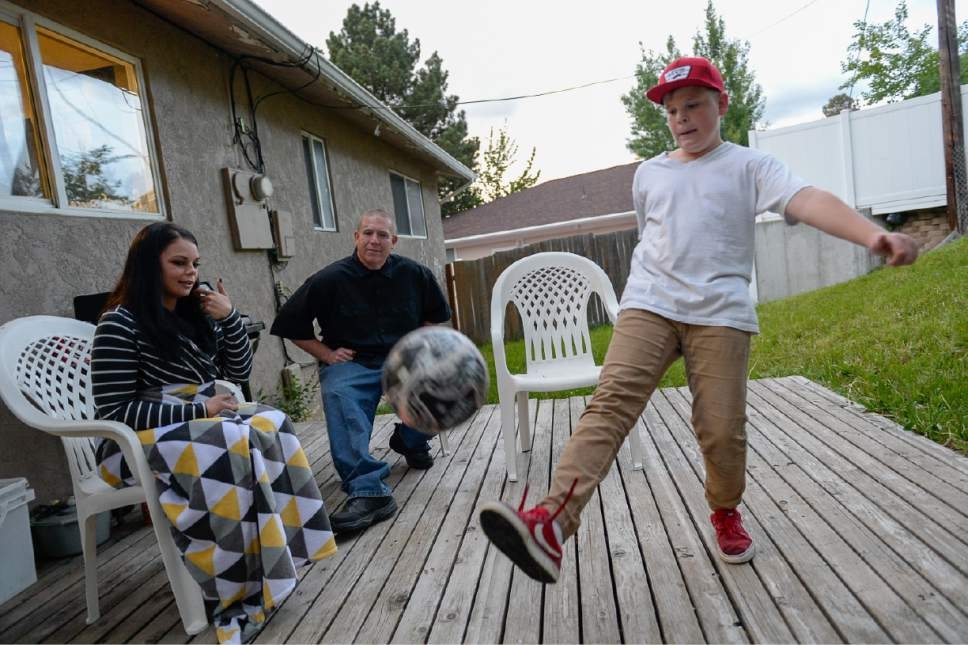 Francisco Kjolseth | The Salt Lake Tribune Lucious Richmond, 12, juggles a soccer in the backyard of their new home in Bountiful as his parents Michael Richmond and Amanda Brunson join him. Both parents have struggled with opioid addiction and have gone through the Davis Behavioral Health treatment program, that was created with the help of Intermountain Healthcare. They both went from living out of their car to purchasing a home and getting their children back after two years of foster care.