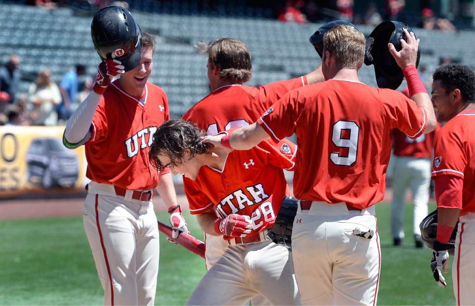 Scott Sommerdorf | The Salt Lake Tribune Team mates mob Utah's Zach Moeller, #28, after his grand slam reduced ASU's lead to 7-6 in the third inning, Sunday, May 28, 2017.