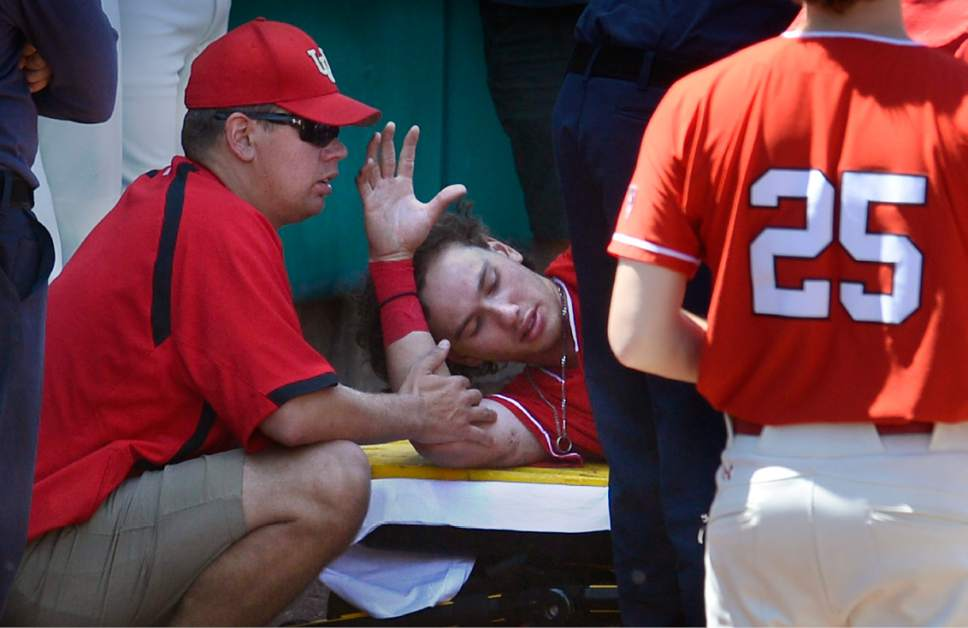Scott Sommerdorf | The Salt Lake Tribune Utah trainer Craig Chelette, left, tends to Utah CF DaShawn Keirsey Jr. after he seriously injured himself trying to make a play on Hunter Bishop's home run during first inning play, Sunday, May 28, 2017. Keirsey was stabilized on the warning track, and then taken away in an ambulance after just two batters in the first inning.