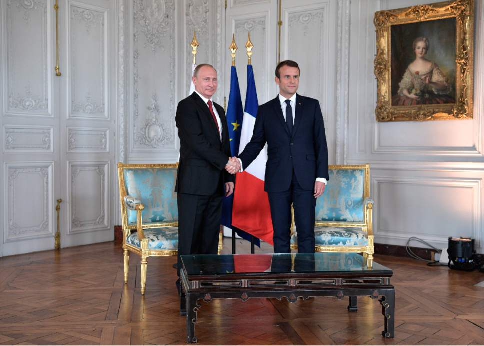 President Emmanuel Macron, right, shakes hands with his Russian counterpart Vladimir Putin as they meet for talks before the opening of an exhibition marking 300 years of diplomatic ties between the two countries at Palace of Versailles, near Paris, France, Monday, May 29, 2017. Monday's meeting comes in the wake of the Group of Seven's summit over the weekend where relations with Russia were part of the agenda, making Macron the first Western leader to speak to Putin after the talks. (Alexei Nikolsky/Pool Photo via AP)