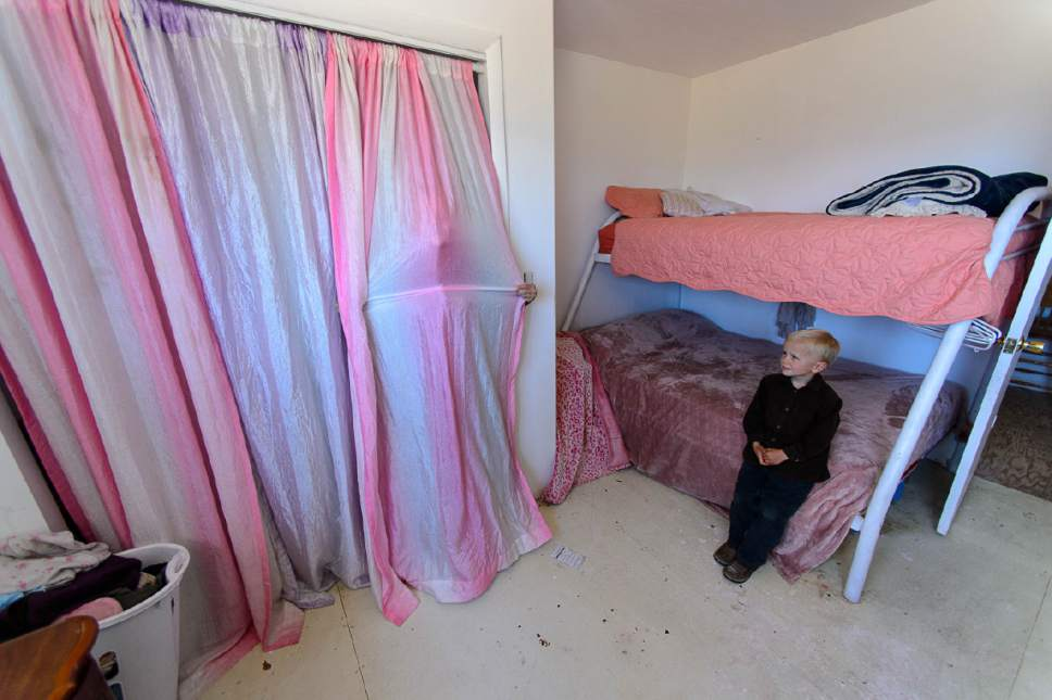 Trent Nelson  |  The Salt Lake Tribune A young FLDS girl peers out from the closet in a room she shares with three sisters in their Cedar City home, Wednesday May 24, 2017. The Johnson family say they relocated to Cedar City after being evicted from UEP Trust properties in Hildale three times.