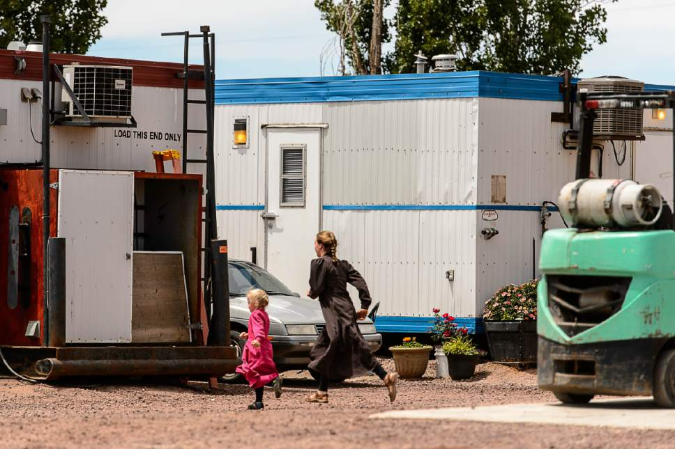 Trent Nelson  |  The Salt Lake Tribune Two FLDS girls run through an industrial yard in Hildale that is lined with trailers where it appears people evicted from UEP Trust properties are temporarily living, Monday May 22, 2017.
