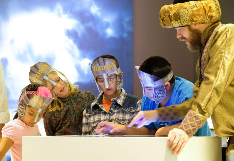 """Francisco Kjolseth   The Salt Lake Tribune Dane Crowton, right, playing the role of Thorgrim, a trader from the north, interacts with kids as part of the hands on exhibit, """"Vikings: Beyond the Legend,"""" a new exhibit at the Natural History Museum of Utah that opens to the public on Saturday and runs through Jan 1. Some 500 artifacts, some of which have never been shown outside Scandinavia are on display."""