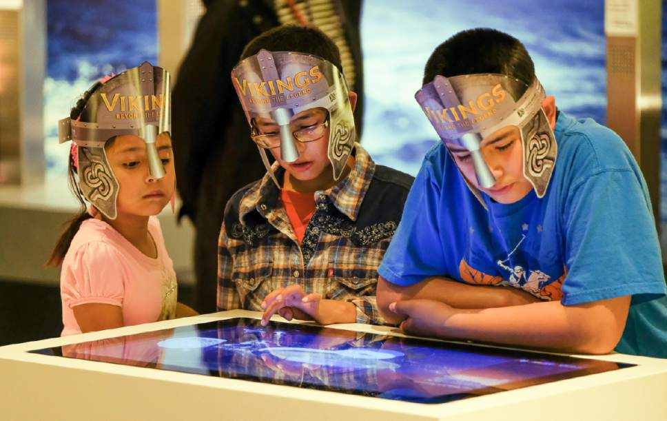 """Francisco Kjolseth   The Salt Lake Tribune Dahlia Avila, 7 and her brothers Jovan, 9, center, and Adrian, 11, get into the spirit of the Viking as they check out one of the interactive displays at the Museum of Natural History of Utah's new exhibit, """"Vikings: Beyond the Legend."""""""