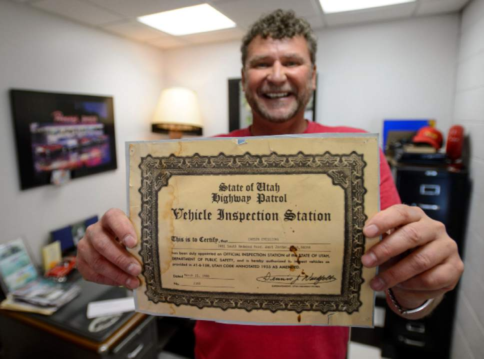 Steve Griffin  |  The Salt Lake Tribune    Mark Carson holds up his original Vehicle Inspection Station certificate from 1988 at Speedway Emissions & Inspection in West Jordan Thursday June 1, 2017. A new law eliminating safety inspections has dedicated safety and emission testing sites nervous for their futures.