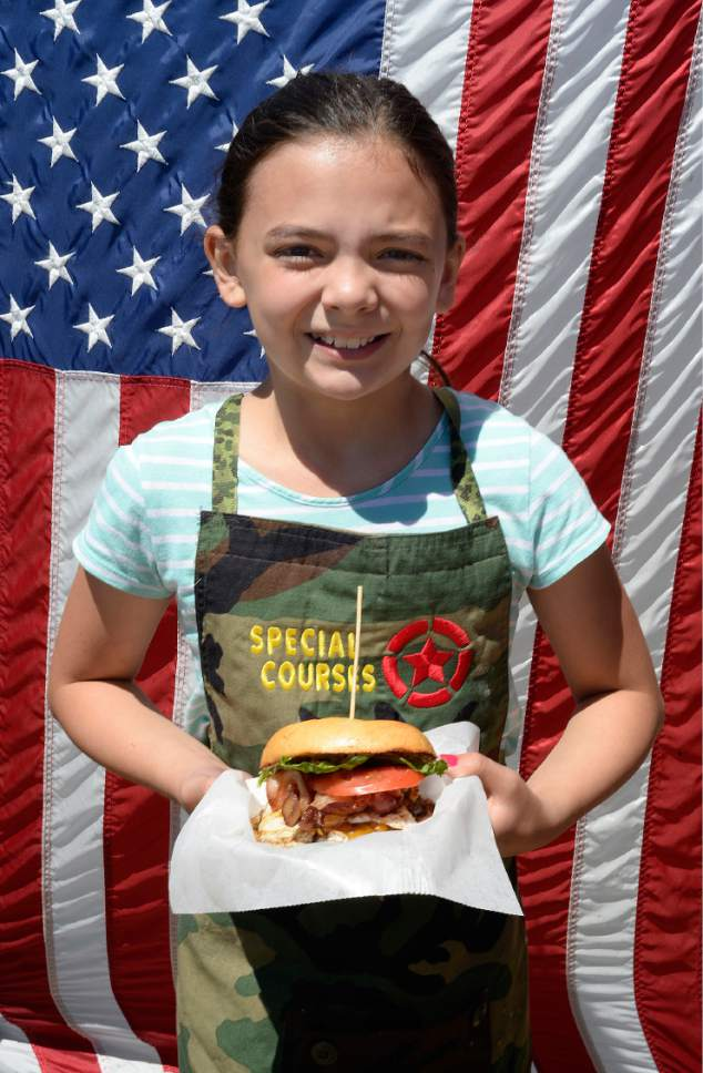 Scott Sommerdorf | The Salt Lake Tribune James Veylupek's daughter Katie, 10, holds a Whiskey-Tango-Foxtrot burger outside the Special Courses food truck, Saturday, May 27, 2017.   Special Courses, is a two-year-old food truck owned by Iraq war veteran James Veylupek, who serves food with a military theme.
