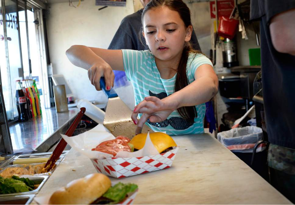 Scott Sommerdorf | The Salt Lake Tribune James Veylupek's daughter Katie, 10, dishes up a burger in the Special Courses food truck, Saturday, May 27, 2017.   Special Courses, is a two-year-old food truck owned by Iraq war veteran James Veylupek, who serves food with a military theme, like the Whiskey-Tango-Foxtrot burger.