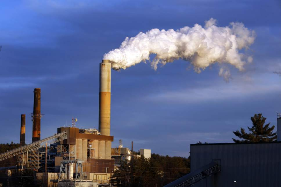FILE - In this Jan. 20, 2015 file photo, a plume of steam billows from the coal-fired Merrimack Station in Bow, N.H. President Donald Trump may abandon U.S. pledges to reduce carbon emissions, but global economic realities ensure he is unlikely to reverse the accelerating push to adopt cleaner forms of energy. (AP Photo/Jim Cole, File)