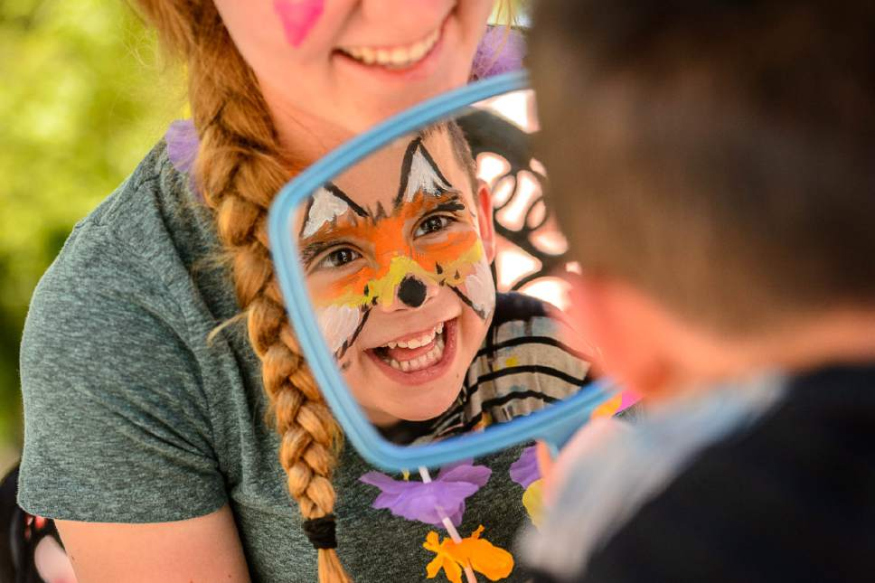 Trent Nelson  |  The Salt Lake Tribune Troy Fryer, 6, tests out his face painting ó a fox ó at Westminster Collegeís Tenth Annual Family Fun Day for children with autism and their families, in Salt Lake City on Saturday as artist Rachel Kuhr watches and smiles.