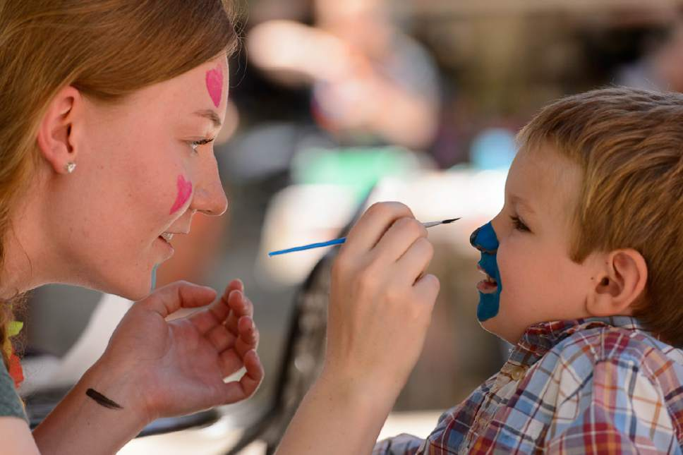 Trent Nelson  |  The Salt Lake Tribune Rachel Kuhr paints Mark Money's face at Westminster College's Tenth Annual Family Fun Day for children with autism and their families, in Salt Lake City, Saturday June 3, 2017.