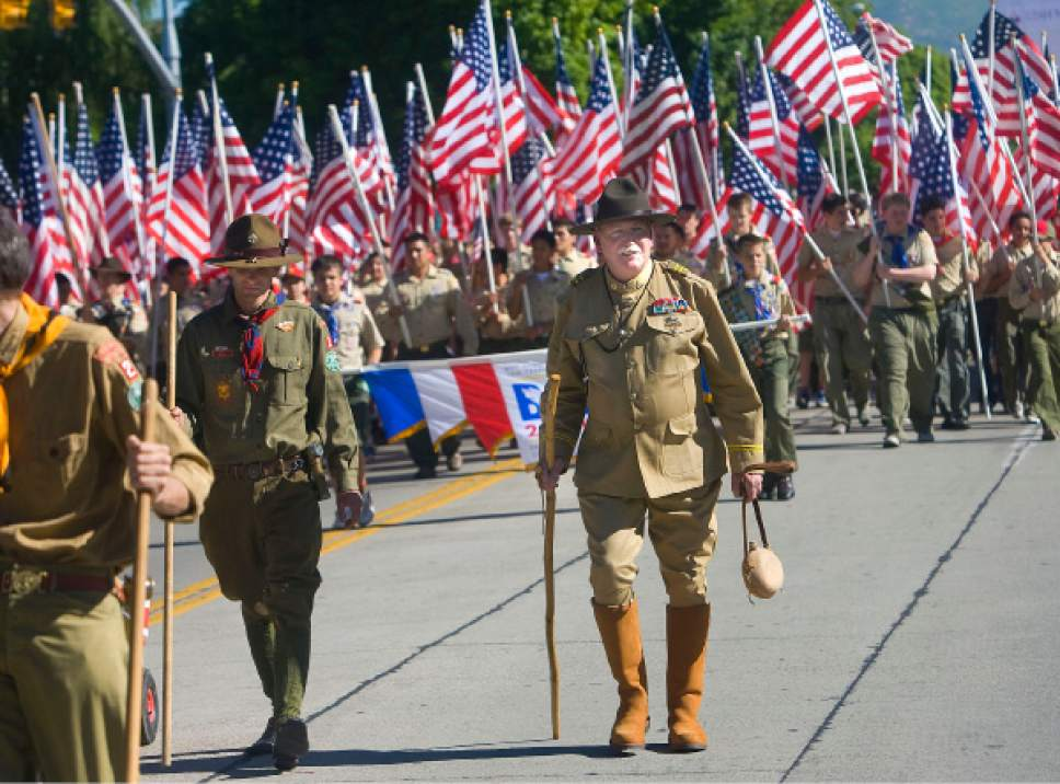 Al Hartmann    Tribune file photo   Boy Scouts both young and old march with an ocean of American flags in the Grand Parade in Provo on Monday, July 5th,  2010.