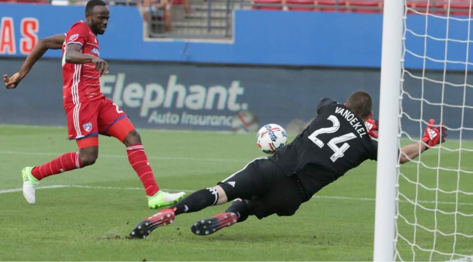 FC Dallas forward Roland Lamah, left, scores a goal against Real Salt Lake goalkeeper Matt Van Oekel (24) during the first half of an MLS soccer match in Frisco, Texas, Saturday, June 3, 2017. (AP Photo/LM Otero)