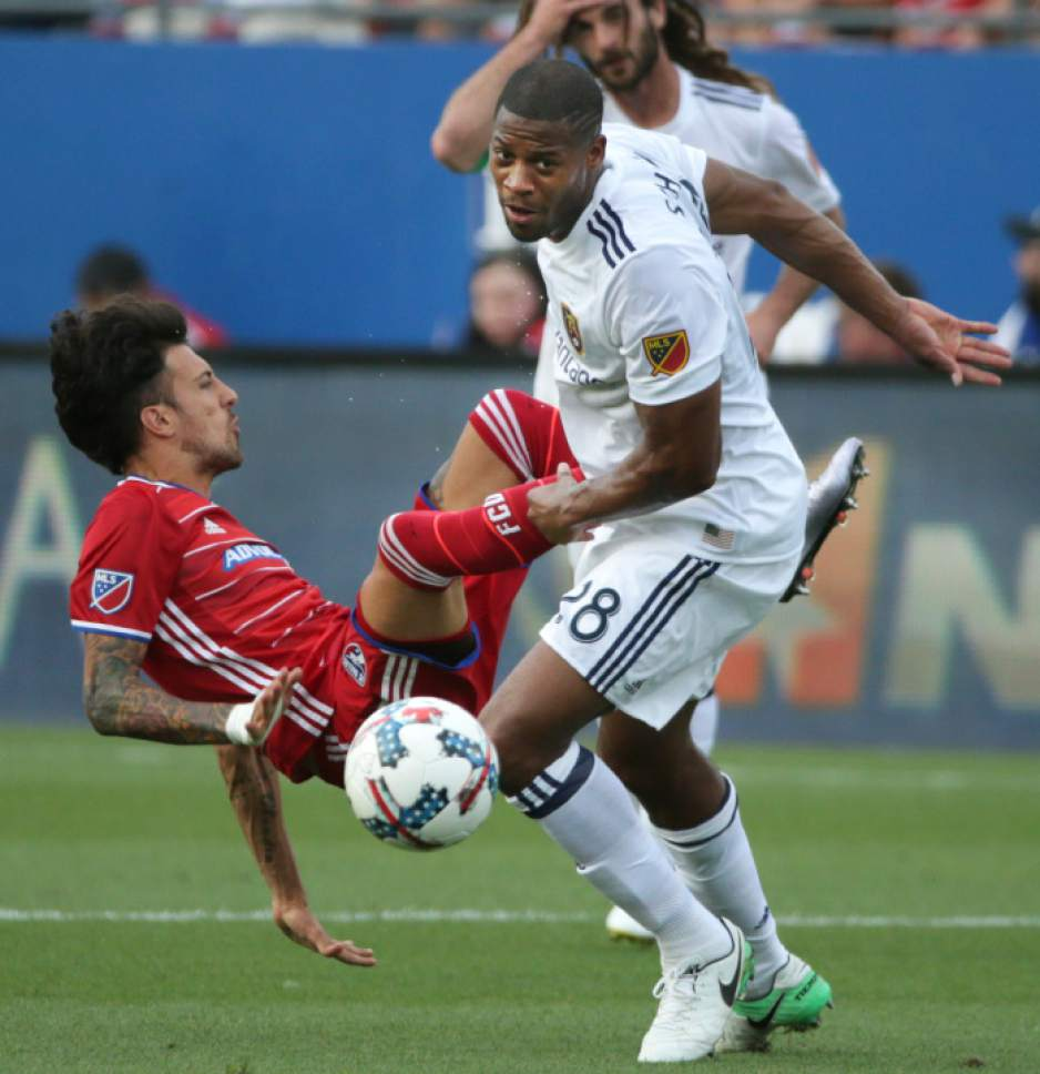 FC Dallas forward Maximiliano Urruti, left, is knocked over by Real Salt Lake defender Chris Schuler (28) during the first half of an MLS soccer match in Frisco, Texas, Saturday, June 3, 2017. FC Dallas won 6-2. (AP Photo/LM Otero)