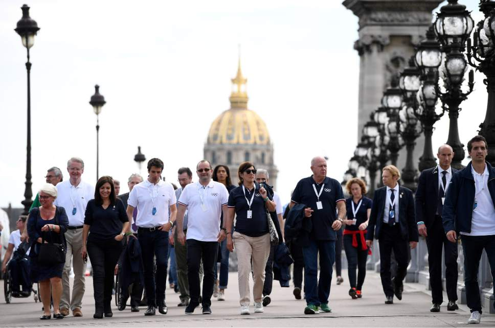 From the left, Co-president of the Paris bid for the 2024 Olympics Bernard Lapasset, Mayor of Paris, Anne Hidalgo, co-president of the Paris bid Tony Estanguet, president of the IOC Evaluation Commission for the 2024 Olympics Patrick Baumann and members of IOC commission, Marisol Casado and Bernard Rajzman walk on the bridge Alexandre III in Paris, Monday May 15, 2017. In background is the Invalides dome. (Franck Fife, Pool via AP)