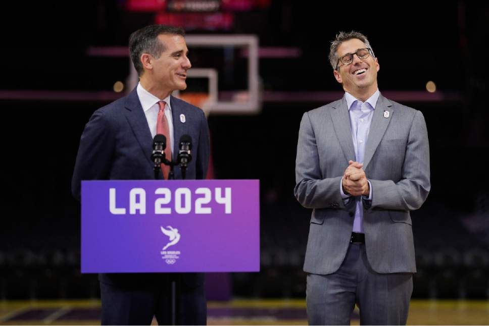 Los Angeles 2024 Chairman Casey Wasserman, right, laughs as he listens to Los Angeles Mayor Eric Garcetti during a news conference at Staples Center, Friday, May 12, 2017, in Los Angeles. The International Olympic Committee officials wrapped up four days of evaluating Los Angeles' bid for the 2024 Games before heading to Paris to check the only other candidate. (AP Photo/Jae C. Hong)