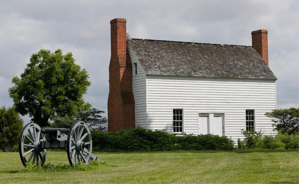 A replica Civil War canon decorates the front lawn of the Flowered Hundred plantation in front of a replica of the original farm home Wednesday, June 7, 2017, in Hopewell, Va. The plantation is one of three Virginia plantations owned buy the family of West Virginia Gov. Jim Justice that will be put on the auction block later this month. (AP Photo/Steve Helber)
