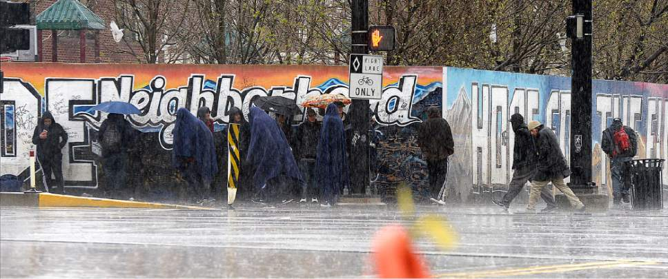 Al Hartmann  |  The Salt Lake Tribune Homeless endure the rain beneath blankets and umbrellas at the intersection of 500 West and 200 South during the pounding rainstorm Monday March 27.