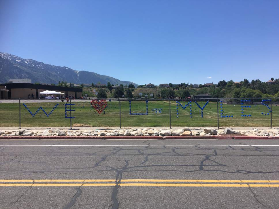 "Tiffany Frandsen | The Salt Lake Tribune  ""We (heart) U Myles"": Message placed by students on a fence at Brookwood Elementary School on June 7, 2017."