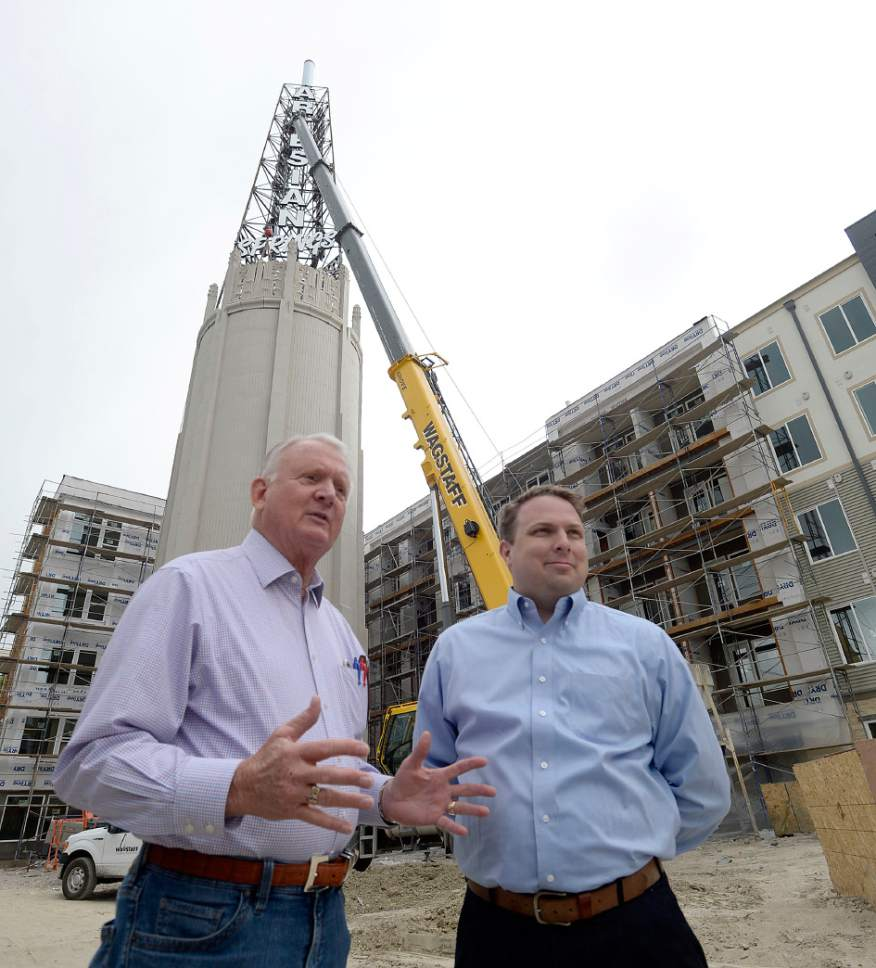 Al Hartmann  |  The Salt LakeTribune Hooper Knowlton, left, and son Bill Knowlton stand in front of the third phase of Artesian Springs, a new affordable housing project at 4200 S. Main St. in Murray.  The apartments haver been developed on the site of the old Murray Laundry tower (in the background.)  The art deco style tower that's been there for decades and a landmark is being restored.