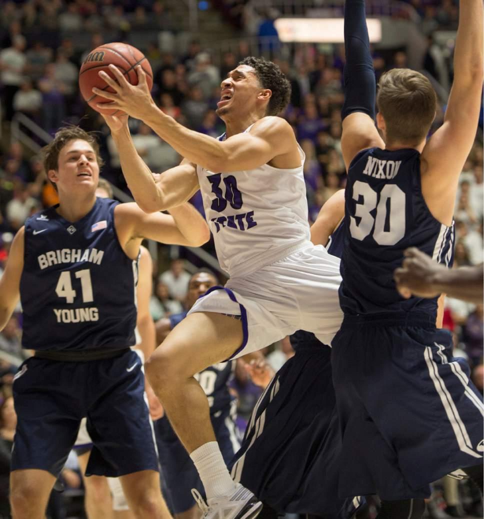 Rick Egan  |  The Salt Lake Tribune  Weber State Wildcats guard Jeremy Senglin (30), splits the defenders, in basketball action BYU vs Weber State, at the Dee Events Center in Ogden, Saturday, December 13, 2014