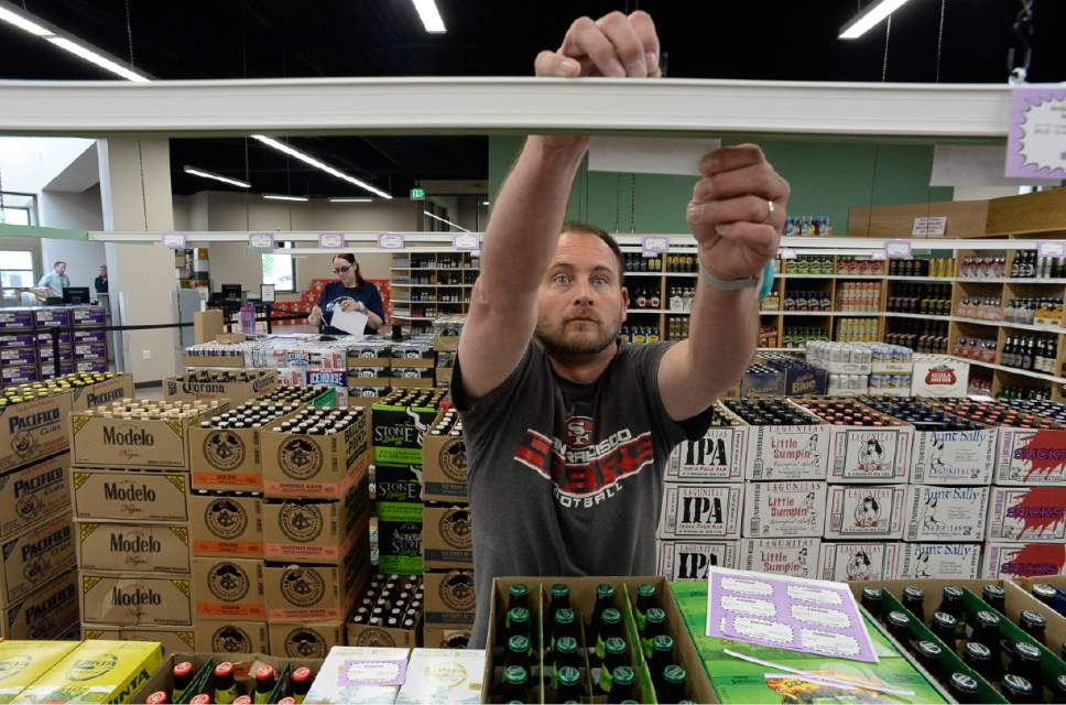Francisco Kjolseth | The Salt Lake Tribune James Brinkerhoff puts up pricing labels over the beer section of Utah's 45th liquor store, as staff put the finishing touches on the new West Valley City store scheduled to open to the public on Tuesday.