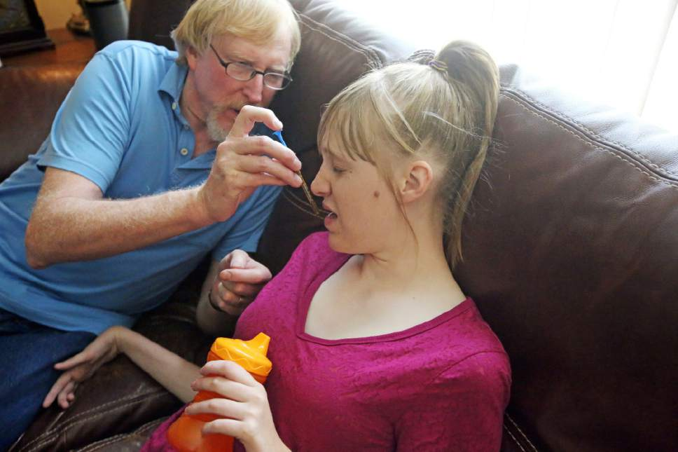 This June 6, 2017, photo, Utah resident Doug Rice administers the CBD oil Haleigh's Hope, a cannabis compound used by his daughter Ashley at their home in West Jordan, Utah. Utah lawmakers balked again this year at joining more than half of all U.S. states and passing a broad medical marijuana law. Rice says Utah's approach means his daughter, who has a genetic condition, is missing out on the one drug that eliminates her frequent seizures. Utah already allows cannabidiol to be used by people with severe epilepsy, as long as they obtain it from other states. (AP Photo/Rick Bowmer)