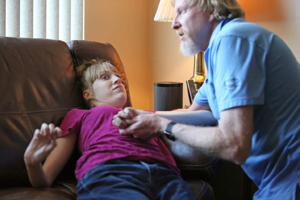 This June 6, 2017, photo, Utah resident Doug Rice, helps his daughter Ashley, 24, during a seizure at their home in West Jordan, Utah. Utah lawmakers balked again this year at joining more than half of all U.S. states and passing a broad medical marijuana law. Rice says Utah's approach means his daughter, who has a genetic condition, is missing out on the one drug that eliminates her frequent seizures. (AP Photo/Rick Bowmer)