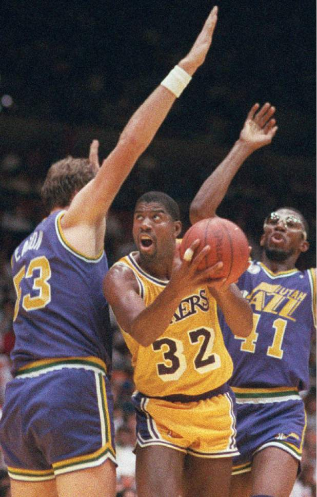 Los Angeles Lakers' Magic Johnson (32) muscles his way between Mark Eaton, left, and Thurl Bailey of the Utah Jazz in Inglewood, Calif., on May 8, 1988.   (AP Photo/Mark Terrill)
