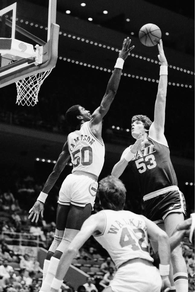 "Utah Jazz 7'4"" center Mark Eaton puts a hook shot up and over the outstretched hand of Houston Rocket center Ralph Sampson in first period action at the Summit in Houston November 11, 1983. (AP Photo/R.J. Carson)"