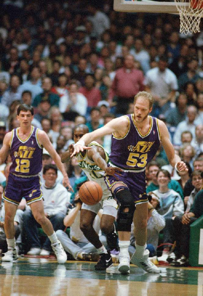 Gary Payton (20) of the Seattle SuperSonics reaches in from behind of knock the basketball away from Mark Eaton (53) of the Utah Jazz during the first quarter of their NBA playoff game, Friday, April 30, 1993, Seattle, Wash. (AP Photo/Robert Sorbo)