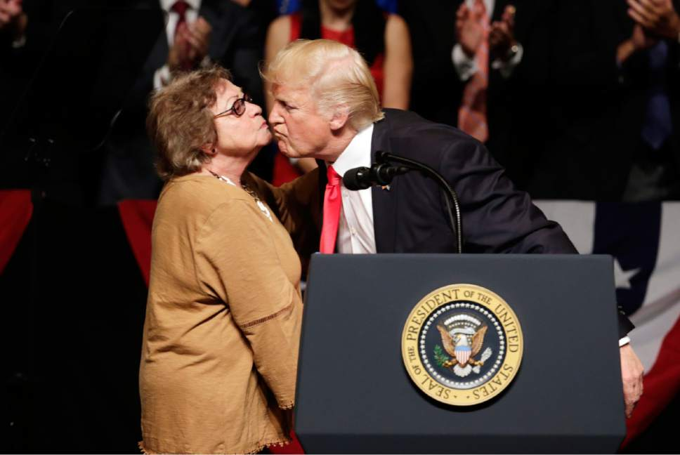 President Donald Trump kisses Martha Beatriz Roque, a Cuban political dissident, during a speech in Miami, Friday, June 16, 2017. Trump announced a revised Cuba policy aimed at halting the flow of U.S. cash to the country's military and security services while maintaining diplomatic relations. (AP Photo/Lynne Sladky)
