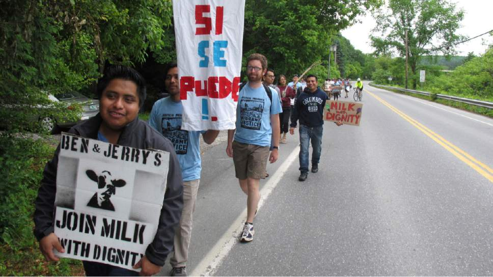 """Scores of dairy farm workers and activists marching in Montpelier, Vt., on Saturday June, 17, 2017. They were marching to the main Ben & Jerry's factory in the Vermont town of Waterbury to protest what they feel are slow negotiations to reach a deal on their """"Milk with Dignity"""" program that would ensure fair wages and living conditions. Ben & Jerry's spokesman Sean Greenwood says the company is committed to reaching a deal with workers. (AP Photo/Wilson Ring)"""