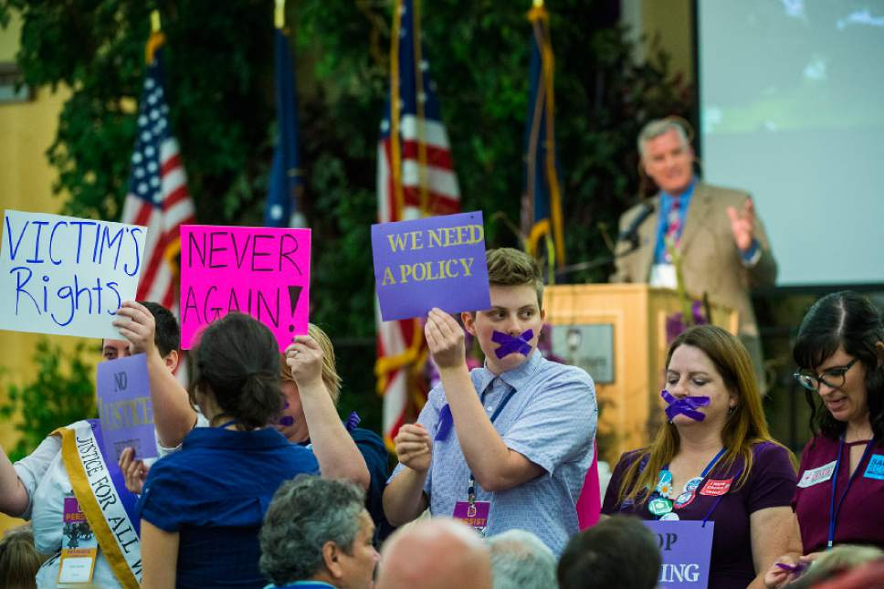 Chris Detrick  |  The Salt Lake Tribune Protestors hold up signs and demonstrate as Chairman Peter Corroon speaks during the Utah State Democratic Party 2017 State Organizing Convention at Weber State University Shepard Union Saturday, June 17, 2017. They were protesting against the Democratic Party's response to the allegations against Rob Miller.