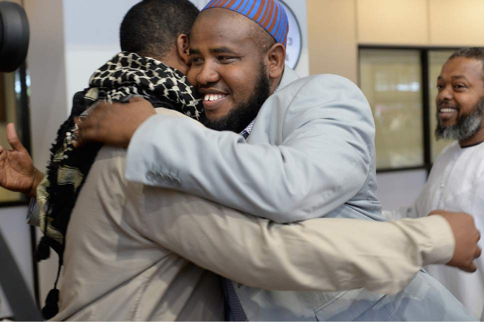 Scott Sommerdorf | The Salt Lake Tribune Imam Yussuf Awadir Abdi gets hugs from friends after he arrived at Salt Lake City International airport, Sunday, June 18, 2017.