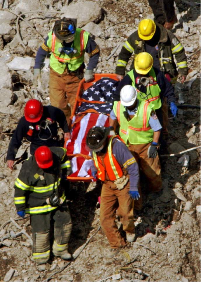 New York firefighters and emergency medical technicians watch their footing as they carry a flag-draped stretcher down a rubble-covered surface after digging a victim from the debris of One World Trade Center, Wednesday, April 10, 2002, in New York.  The remains of at least three other people were found in the same area Tuesday. (AP Photo/Kathy Willens)