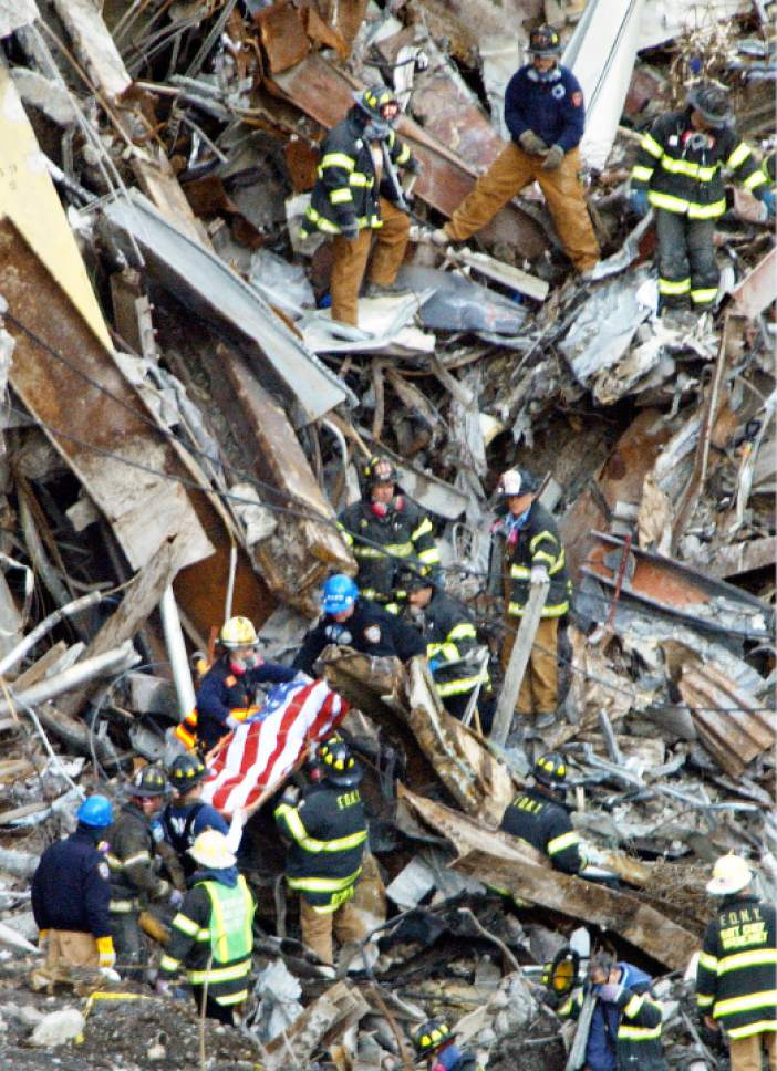 The flag-draped body of a victim of the World Trade Center attacks is taken from the rubble by members of the New York City Fire Department Thursday, Jan. 10, 2002, in New York. Nearly 4 months after the Sept. 11, 2001 terrorist attacks, remains of the victims continue to be found. The latest count of victims released by city officials Wednesday, Jan. 9, 2002, stands at 2,893.(AP Photo/Beth A. Keiser)