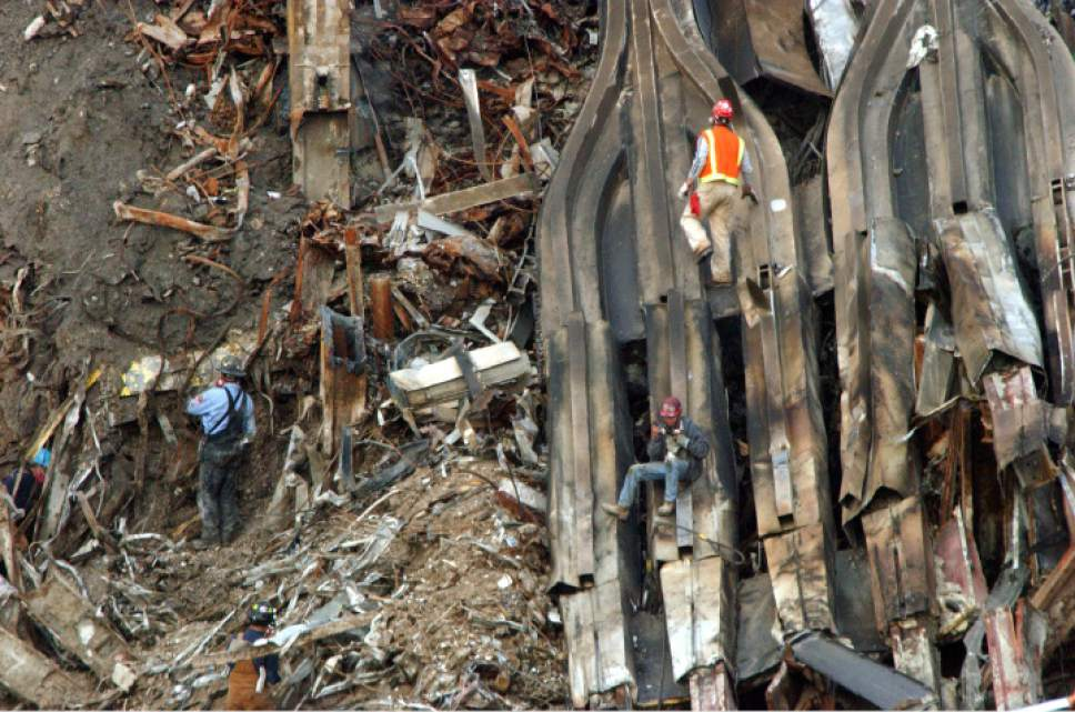 Two workers work on a large section of the facade of Tower One, at right, as a firefighter examines the rubble at the site of  the World Trade Center Disaster, Friday, Nov. 16, 2001, in New York. Homeland security Director Tom Ridge, standing next to rumbling machinery in the World Trade Center rubble, on Friday affirmed the Bush administration's commitment to $20 billion in aid to the city. (AP Photo/ Louis Lanzano)