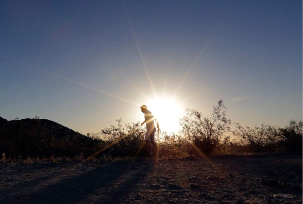 FILE - In this June 16, 2017, file photo, a man runs through section of South Mountain Park at sunrise to avoid the excessive heat in Phoenix. A record heat wave is rolling into Arizona, Utah, Nevada and California. The southwestern U.S. is about to feel the wrath of a punishing heat wave. (AP Photo/Matt York, File)