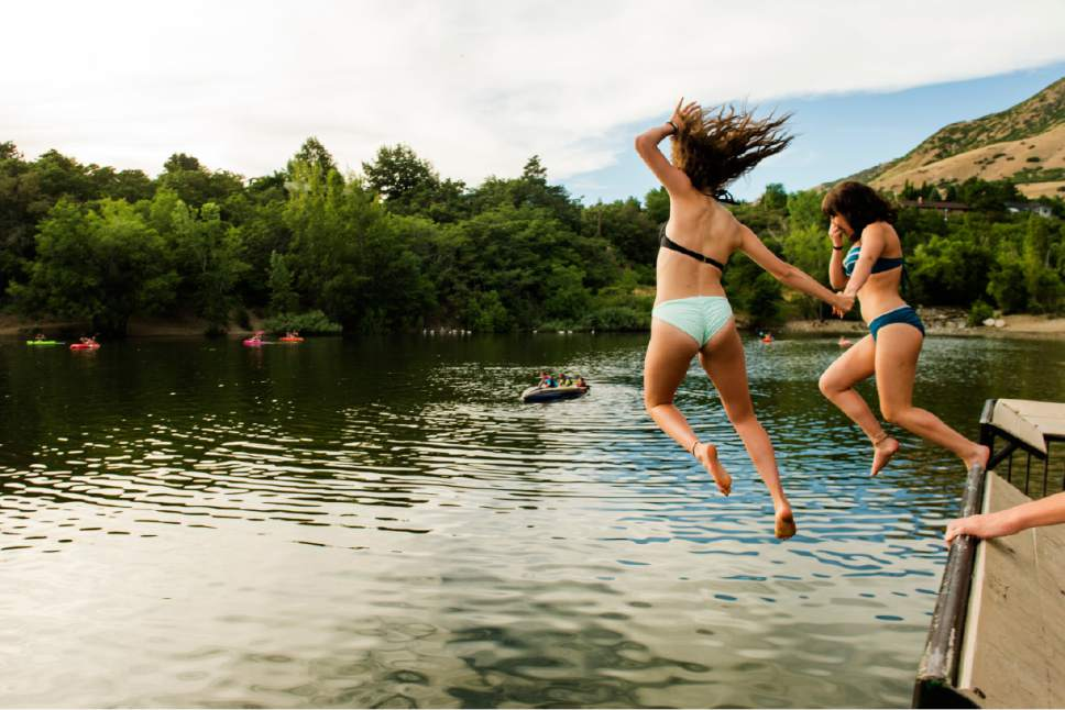 Rick Egan  |  The Salt Lake Tribune  Ashley Hubert holds hands with Alexis Archuleta, as they jumping into Farmington Pond to cool off, Monday, June 19, 2017.