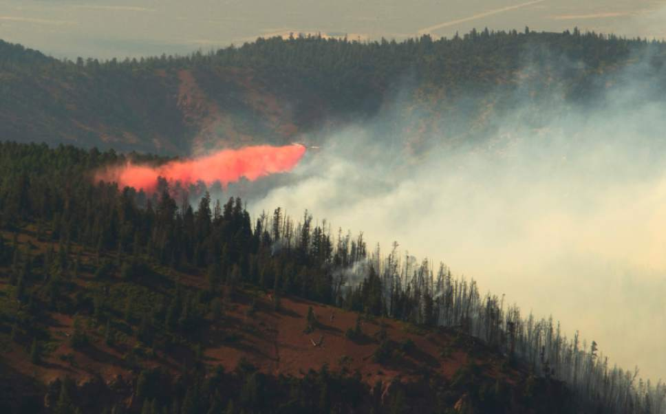 Rick Egan     The Salt Lake Tribune  A plane drop fire retardant on the Brian Head fire, as it continues to burn north of the southern Utah ski town of Brian Head, Wednesday, June 21, 2017.