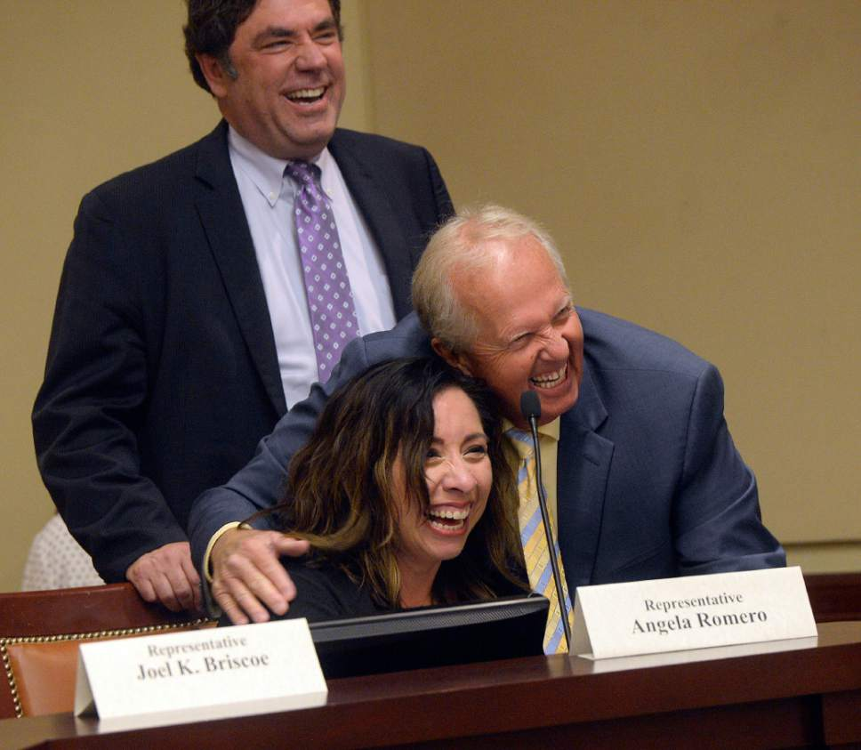 Al Hartmann  |  The Salt LakeTribune  Rep. Angela Romero, D, left, gets a hug from Michael Noel, R before the start of an unusual open caucus meeting with both parties to discuss a power struggle lawmakers are having with Gov. Gary Herbert at the state capitol Tuesday June 20.  House Minority Leader Brian King, D, at top. The committee discussed whether Herbert overstepped his bounds in not allowing the attorney general to give an opinion to them on legality of process the governor imposed for a special election to replace Rep. Jason Chaffetz.