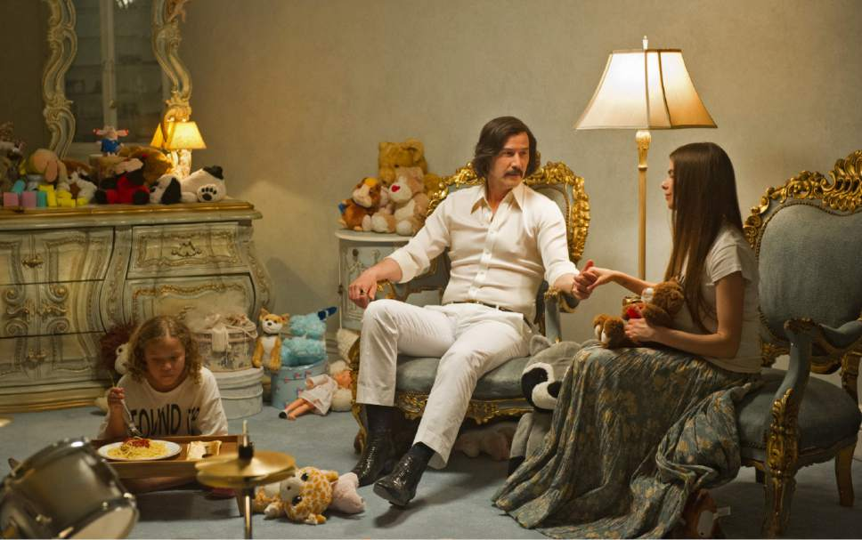 """The Dream (Keanu Reeves), a charismatic cult leader, entertains guests in his mansion, in a scene from the dystopian horror-thriller """"The Bad Batch."""" Courtesy Neon Films"""