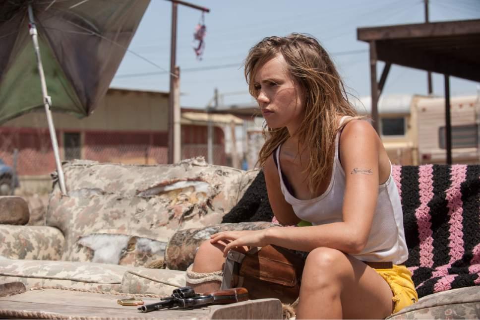 "Arlen (Suki Waterhouse) loads her revolver, in a scene from the dystopian horror-thriller ""The Bad Batch."" Courtesy Neon Films"